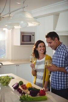 Casal segurando copos de vinho na cozinha