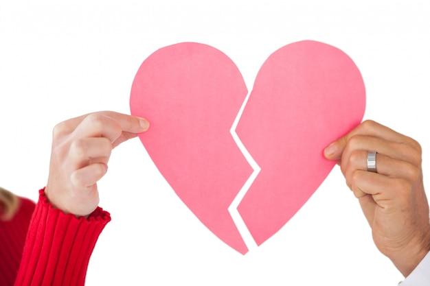 Casal segurando duas metades de coração partido