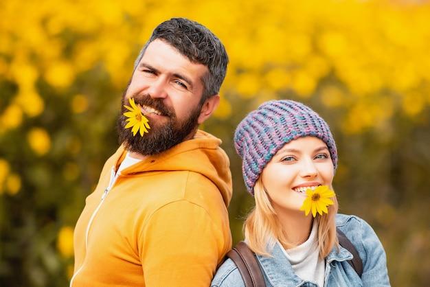 Casal segurando flores na boca ao ar livre