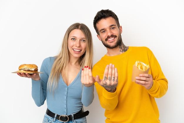 Casal segurando hambúrguer e batatas fritas sobre fundo branco isolado, convidando para vir com a mão. feliz que você veio