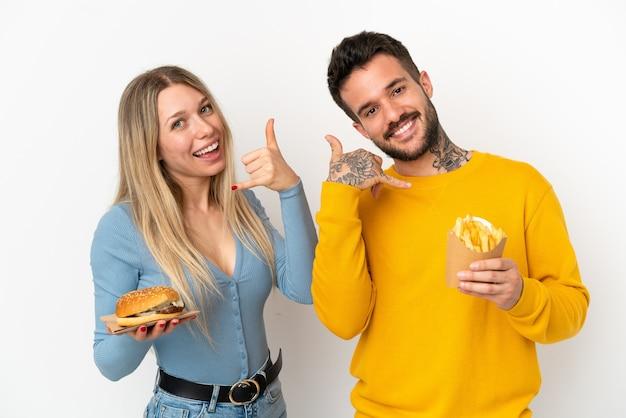 Casal segurando hambúrguer e batatas fritas sobre fundo branco isolado, fazendo gesto de telefone. ligue-me de volta sinal