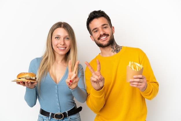 Casal segurando hambúrguer e batatas fritas sobre fundo branco isolado, sorrindo e mostrando sinal de vitória