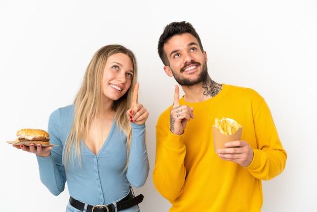Casal segurando hambúrguer e batatas fritas sobre um fundo branco isolado apontando com o dedo indicador uma ótima ideia