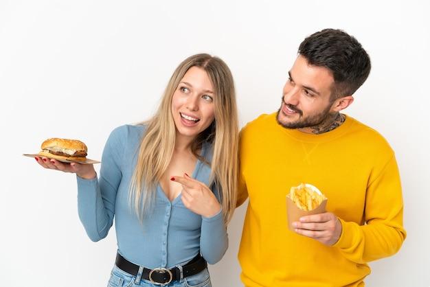 Casal segurando hambúrguer e batatas fritas sobre um fundo branco isolado apresentando uma ideia enquanto olha sorrindo para