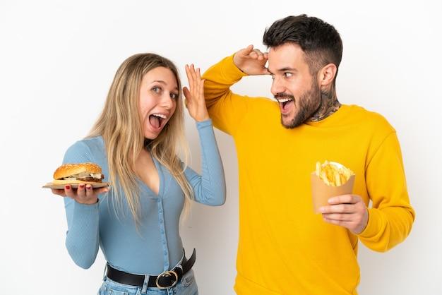 Casal segurando hambúrguer e batatas fritas sobre um fundo branco isolado com expressão facial de surpresa e choque