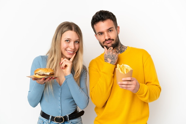 Casal segurando hambúrguer e batatas fritas sobre um fundo branco isolado sorrindo com uma expressão doce