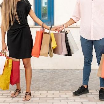 Casal segurando juntos sacos de compras