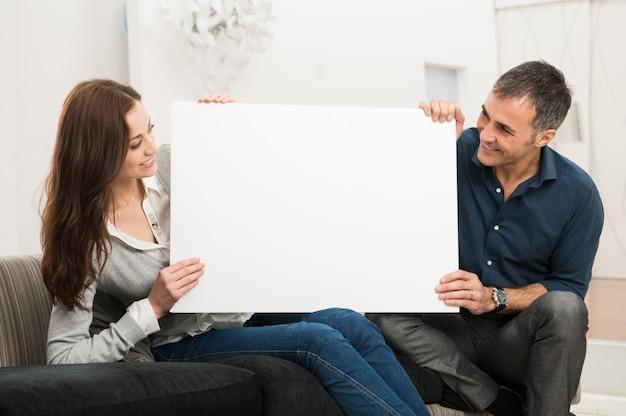 Casal segurando o cartaz