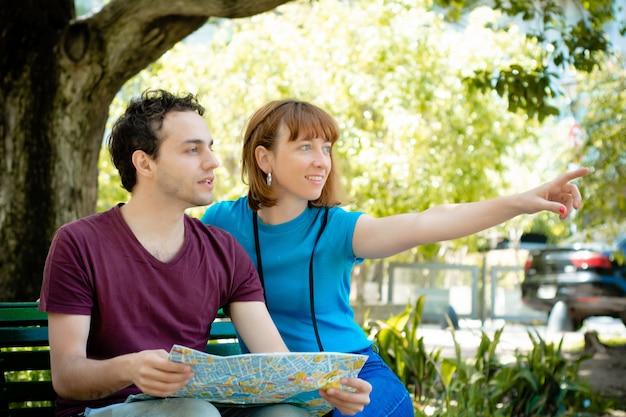 Casal segurando o mapa nas mãos e viajando juntos.