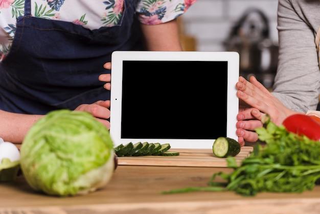 Casal segurando o tablet com tela para a câmera