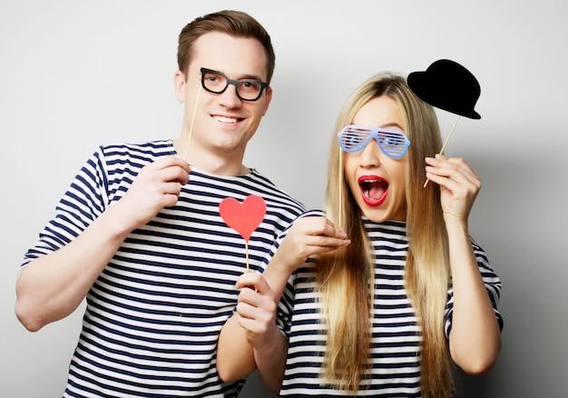 Casal segurando óculos e chapéu de festa em varas