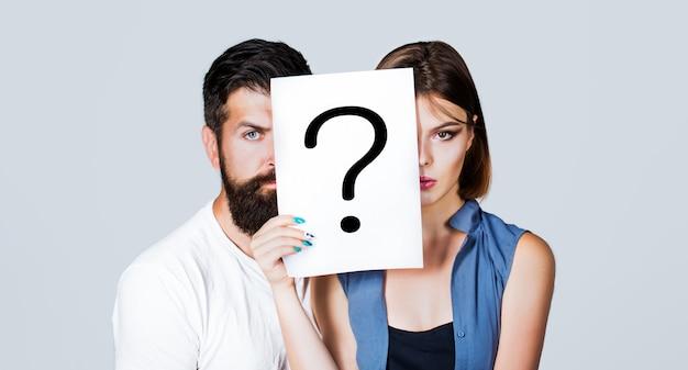 Casal segurando papel ponto de interrogação. anônimo, pergunta de homem e mulher, incógnita.
