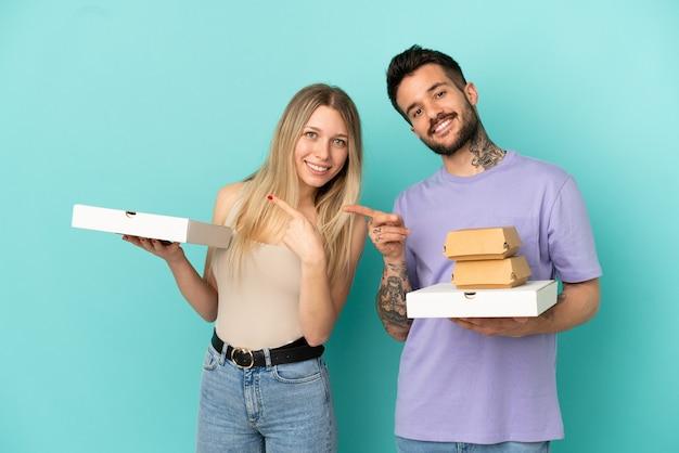 Casal segurando pizzas e hambúrgueres sobre fundo azul isolado apontando o dedo para o lado na lateral
