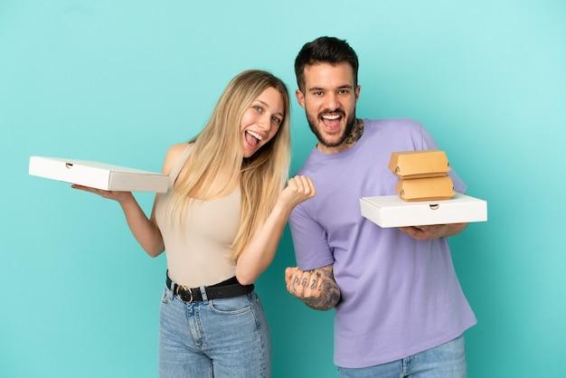 Casal segurando pizzas e hambúrgueres sobre fundo azul isolado comemorando vitória