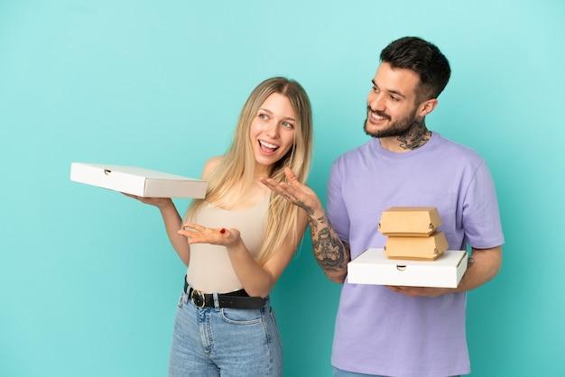 Casal segurando pizzas e hambúrgueres sobre um fundo azul isolado, apontando para trás e apresentando um produto
