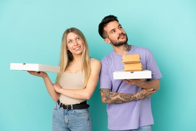 Casal segurando pizzas e hambúrgueres sobre um fundo azul isolado olhando para cima enquanto sorri