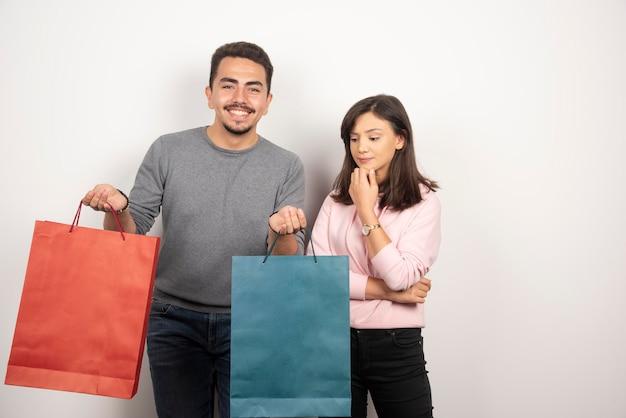 Casal segurando sacolas de compras em branco.