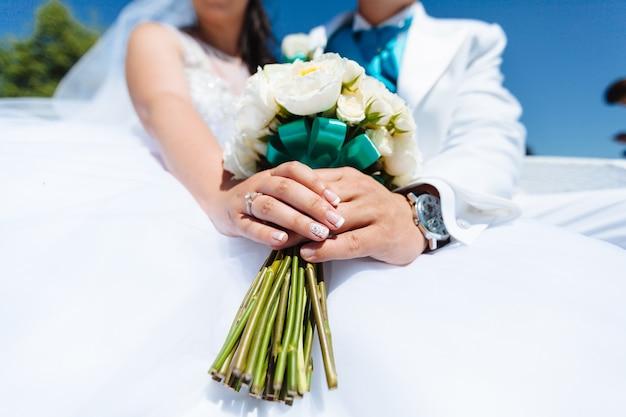 Casal segurando um buquê de flores com as duas mãos
