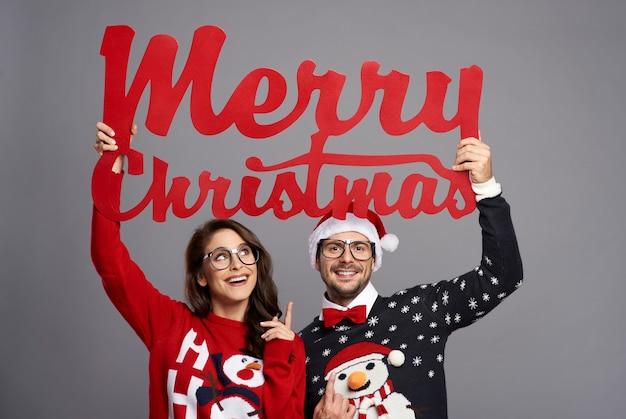 Casal segurando uma grande placa dizendo feliz natal
