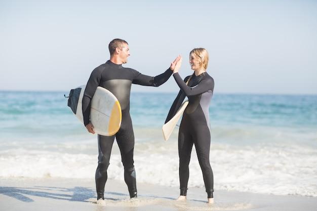 Casal segurando uma prancha de surf e dando cinco uns aos outros