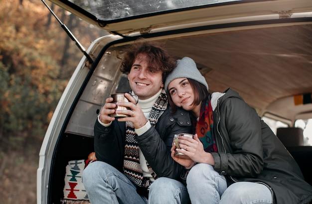 Casal segurando xícaras de café em uma van