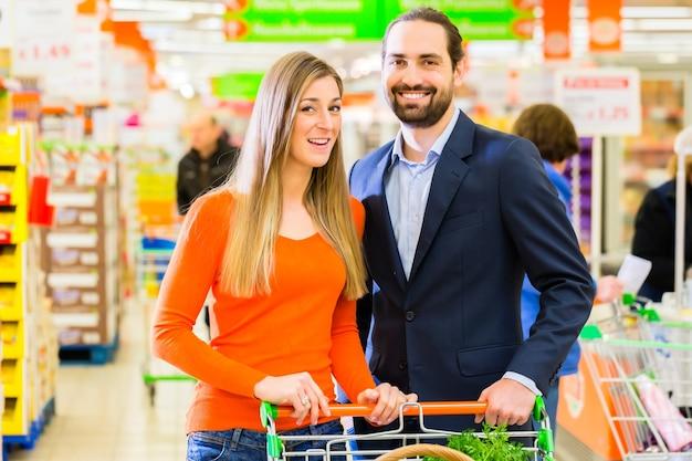 Casal selecionando laticínios enquanto faz compras no supermercado