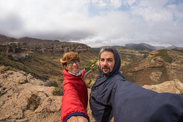 Casal selfie com os braços estendidos, cimeira de montanha de vento