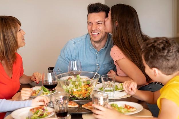 Casal sendo romântico em jantar em família