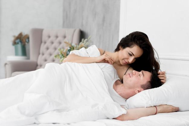 Casal sendo romântico na cama em casa