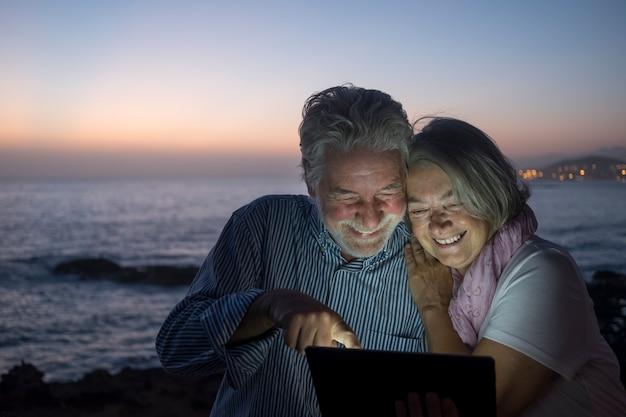 Casal sênior alegre de pessoas rindo juntos, olhando para o tablet enquanto está sentado na praia ao entardecer. atrás deles, a costa acende-se para a noite