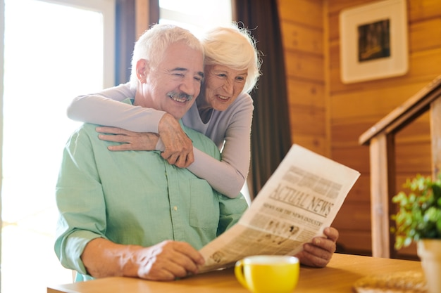 Casal sênior alegre em trajes casuais lendo as últimas notícias da manhã em sua casa de campo