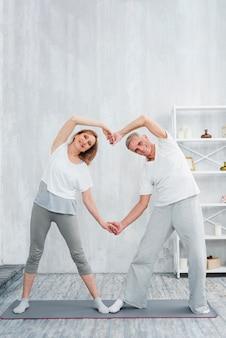 Casal sênior alegre fazendo formato de coração com as mãos durante o exercício em casa