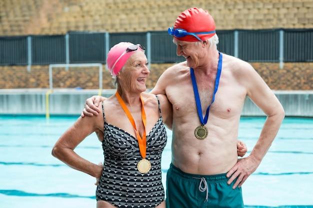 Casal sênior alegre usando medalhas ao lado da piscina