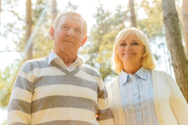 Casal sênior alegre. vista de baixo ângulo de um casal alegre de idosos olhando para a câmera e sorrindo enquanto está perto um do outro ao ar livre