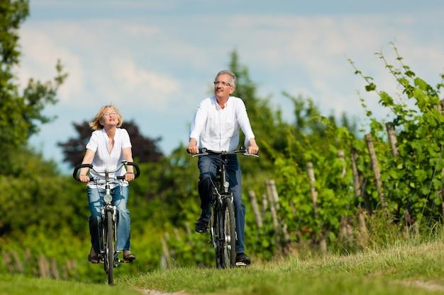Casal sênior, andar de bicicleta no verão
