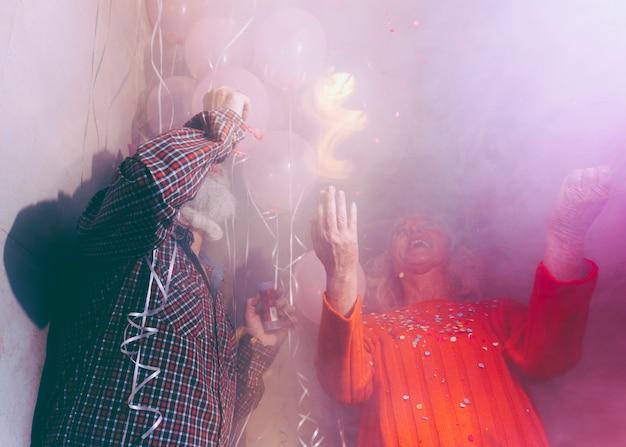 Casal sênior, aproveitando a festa de aniversário na sala cheia de fumaça