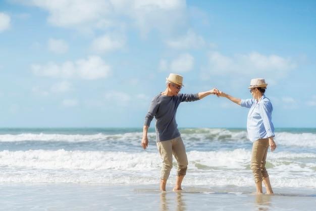 Casal sênior asiático dançando na praia. lua de mel idosa juntos muito felicidade após a aposentadoria. plano de seguro de vida. atividade após a aposentadoria no verão