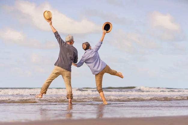 Casal sênior asiático pulando na praia. lua de mel idosa juntos muito felicidade após a aposentadoria. plano de seguro de vida. atividade após a aposentadoria no verão
