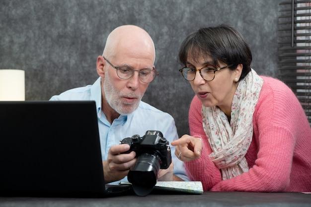 Casal sênior assistindo fotos de férias na câmera