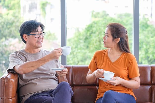 Casal sênior bebendo café, conversando e sorrindo enquanto está sentado perto da janela em casa.