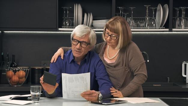 Casal sênior calcula suas contas na cozinha