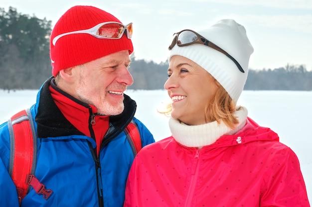 Casal sênior caminhando com bastões de caminhada nórdica em um parque de inverno nevado
