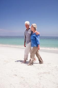 Casal sênior caminhando na praia