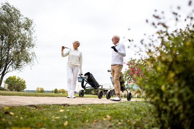 Casal sênior carregando equipamento de golfe e seguindo para a zona verde para continuar jogando.