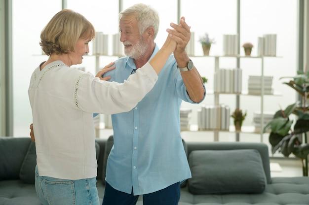 Casal sênior caucasiano feliz dançando em casa
