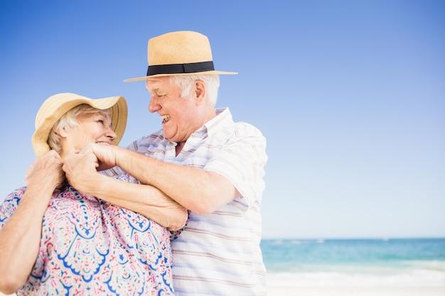 Casal sênior com chapéu abraçando