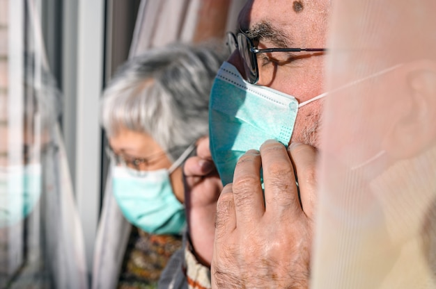 Casal sênior, com máscaras protetoras, em casa olhando pela janela. conceito de quarentena de coronavírus ficar em casa e distanciamento social.