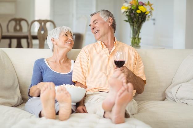 Casal sênior com pipoca e copo de vinho na sala de estar