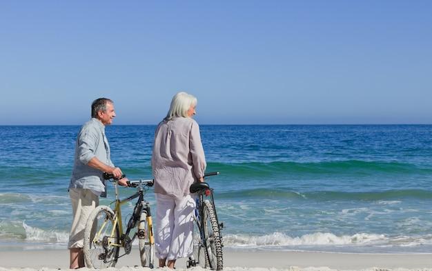 Casal sênior com suas bicicletas na praia