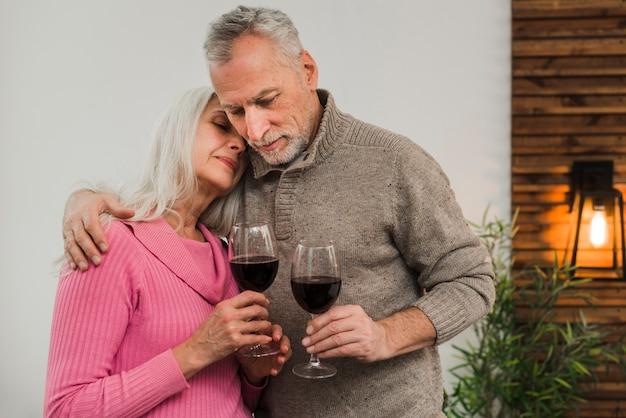 Casal sênior comemorando o dia dos namorados com vinho